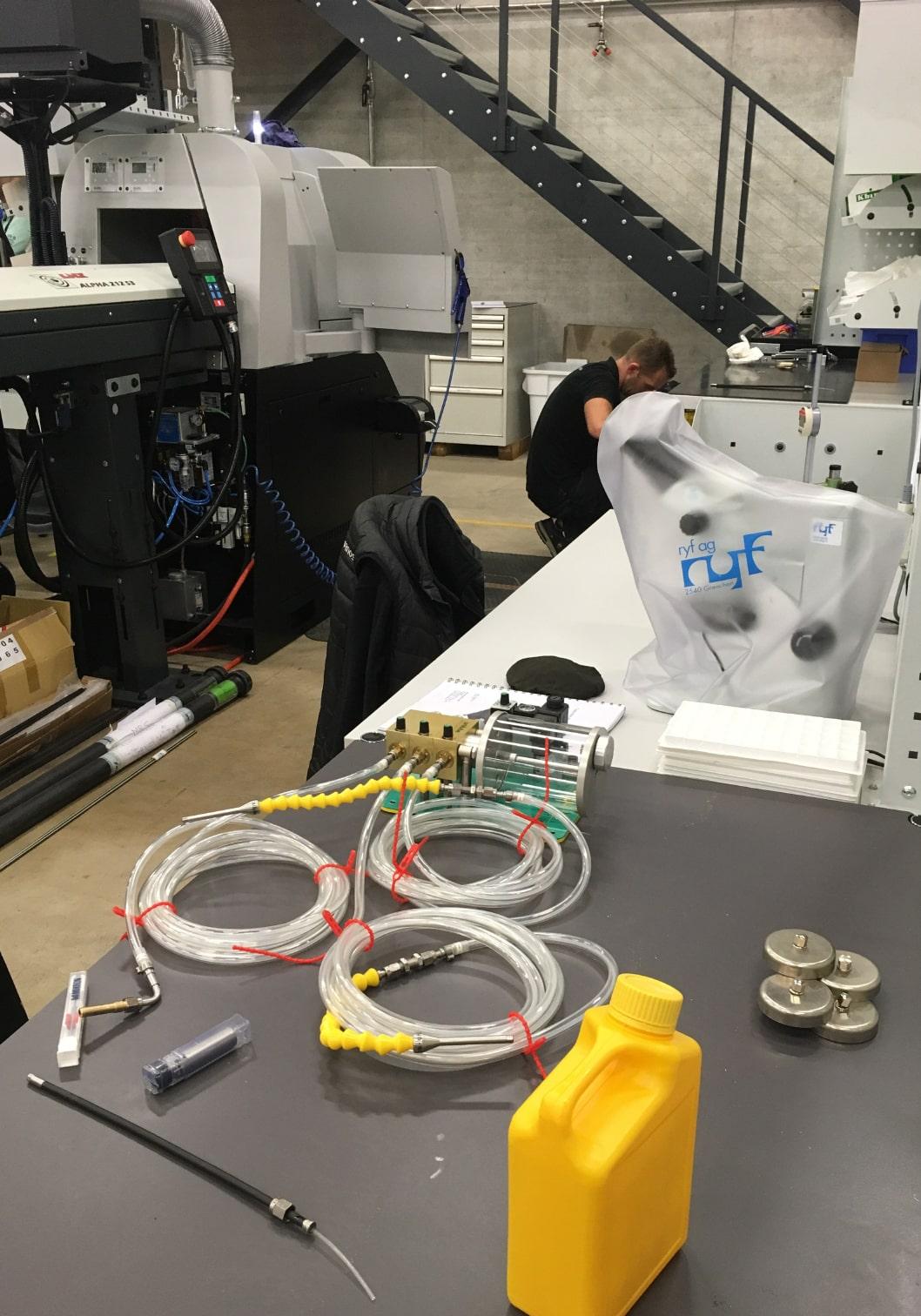 Zeigt die Vorbereitungen zum Test von Unilube Minimalmengenschmierung auf einer Tornos Drehmaschine.