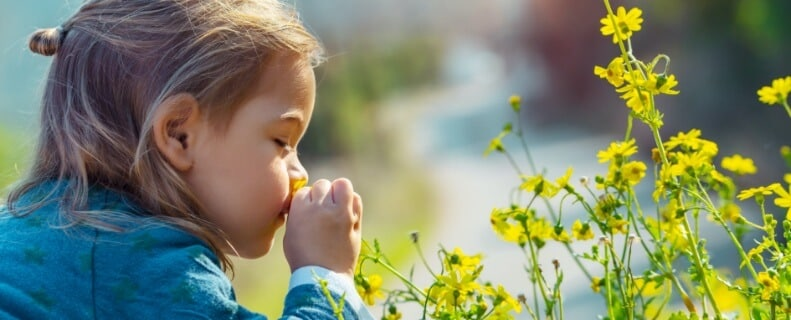 Zeigt ein junges Mädchen welches an einer gelben Blume riecht. Sinnbild für die umweltfreundlichen Produkte im Bereich der Minimalmengenschmierung von UNILUBE.