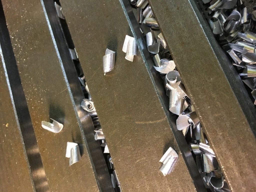 Zeigt Aluminiumspäne auf einem Maschinentisch nach dem Einsatz von Unilube Minimalmengenschmierung.