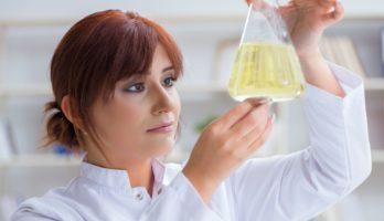 Zeigt eine Chemikerin beim Betrachten einer Schmierstoffprobe in einem Erlenmeyerkolben. Symbolbild für die Hochleistungsschmierstoffe von Unilube.