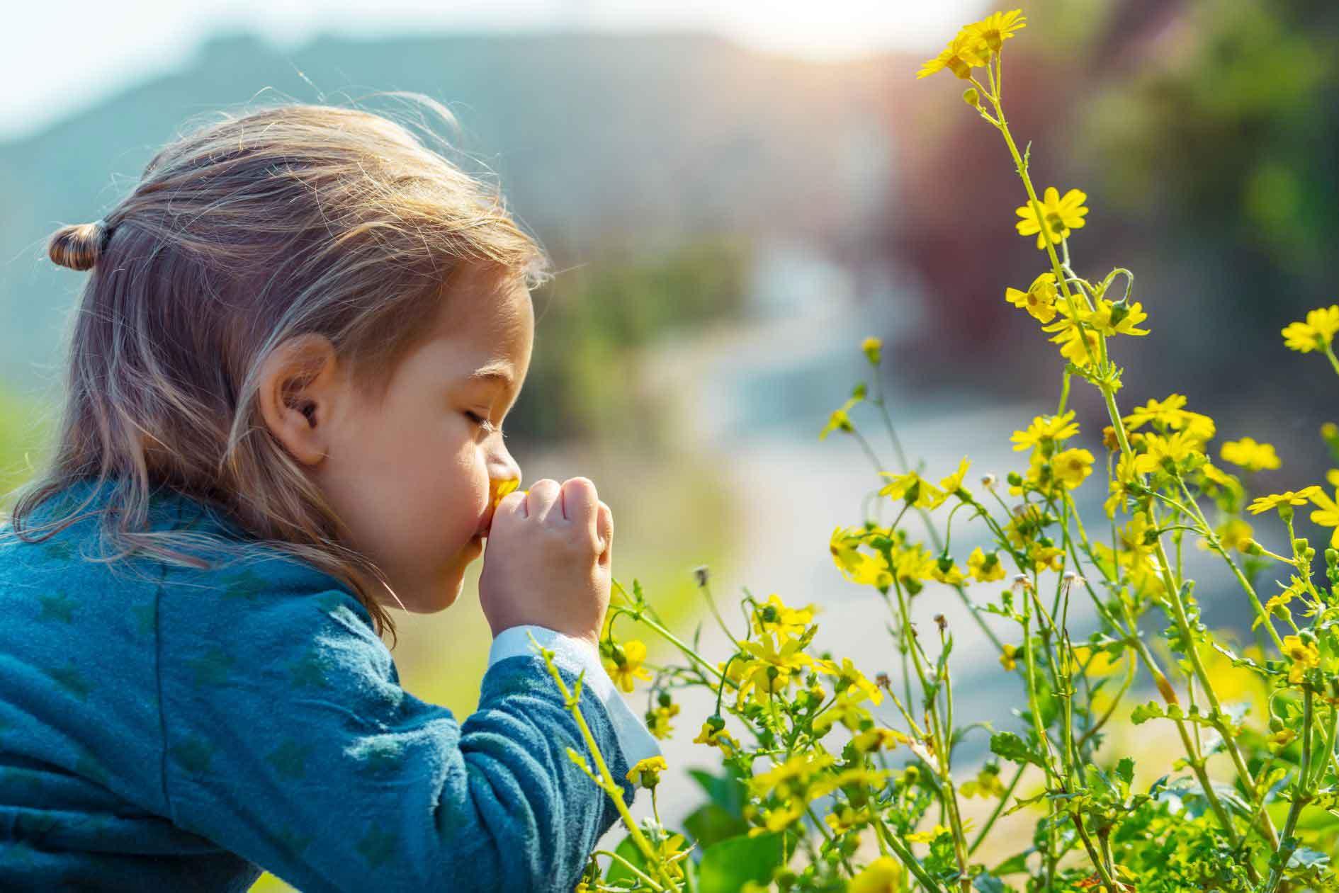 Zeigt ein junges Mädchen welches an einer gelben Blume riecht. Symbolbild für die umweltfreundlichen Produkte im Bereich der Minimalmengenschmierung von Unilube.