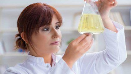 Zeigt eine Chemikerin beim Betrachten einer Schmierstoffprobe in einem Erlenmeyerkolben. Sinnbild für die Hochleistungsschmierstoffe von Unilube.